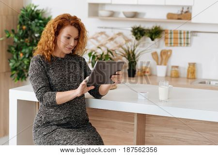 Browsing the net. Full term pregnant woman wearing dress sitting in the kitchen and using a tablet while having a lunch at home.