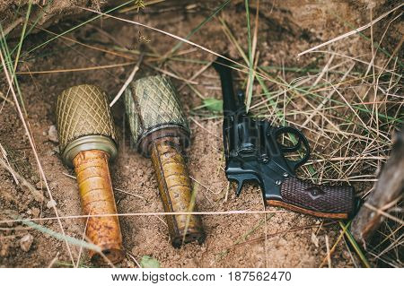 Soviet Red Army Russian Soldiers Military Ammunition Of World War II On Ground. Two Grenades And Nagant Handgun Gun.