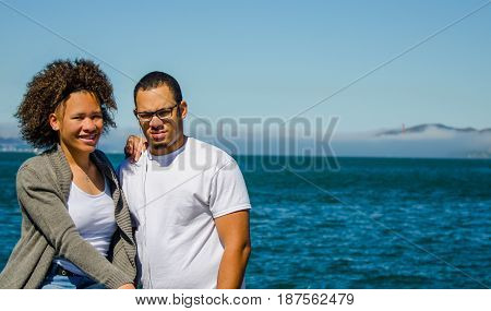 Brother and sister poses with Golden Gate Bridge in background view