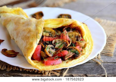 Omelette with mushrooms and tomatoes. Home omelette with fried mushrooms, fresh tomatoes and dill greens on a plate and vintage wooden table. Stuffed vegetarian omelette idea. Rustic style. Closeup