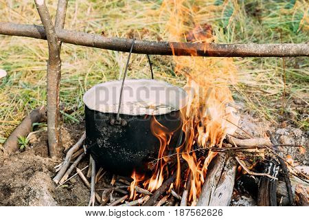 Old Retro Camp Saucepan Boiled Water For Soup Preparation On A Fire In Forest. Flame Fire Bonfire At Summer Day .