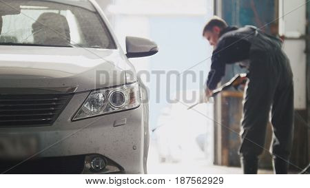 Worker washes the car in workshop - manual labour, telephoto