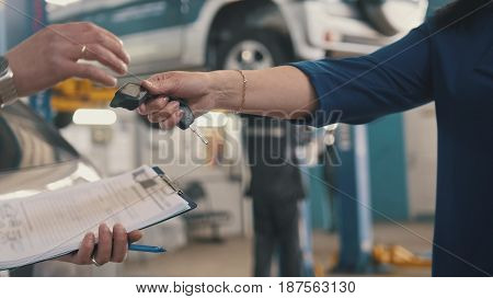 Car workshop - client gives the keys of automobile for mechanic, telephoto