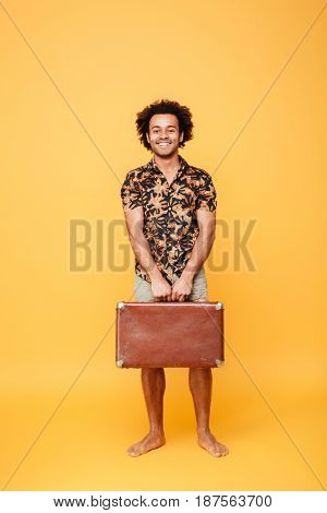 Full length portrait of a smiling happy afro american man in summer clothes holding suitcase and looking at camera isolated over yellow background