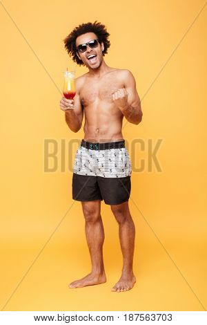 Picture of young happy african man dressed in shorts standing isolated over yellow background. Looking at camera drinking cocktail showing winner gesture.