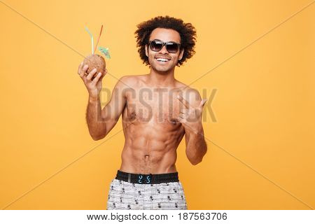 Image of happy young african man dressed in shorts standing isolated over yellow background. Looking at camera drinking cocktail and pointing.