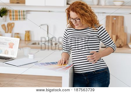 Hard decision. Mature future mom leaning on table with her hand on a belly while choosing the colours to paint a baby room.