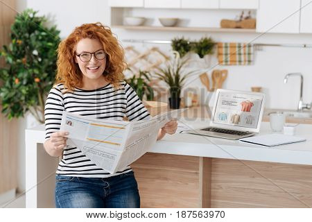 Current news. Positive expectant mother smiling while working from home and reading the latest news from a newspaper