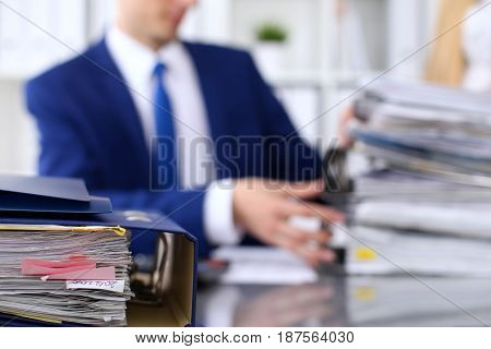 Binders with papers are waiting to be processed with businessman and secretary back in blur. Accounting planning budget, audit, insurance and business concept.