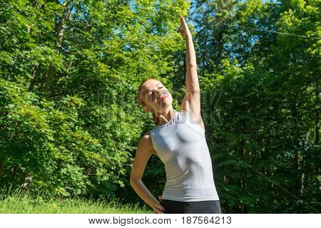 Sensuous slim woman doing fitness in park