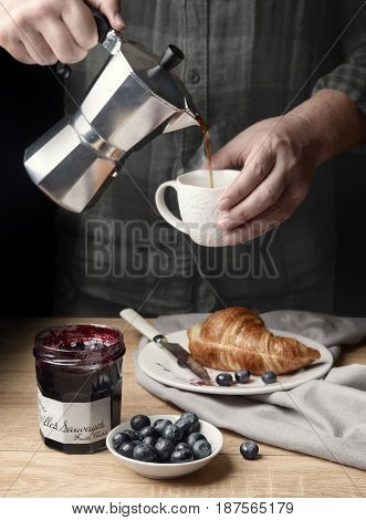 Morning coffee with a haze with croissant and blueberry jam on a wooden table