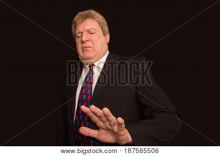 Serious senior businessman showing stop gesture With disgust on his face