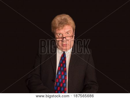 The Senior Business Man with glasses looking at camera on black studio background
