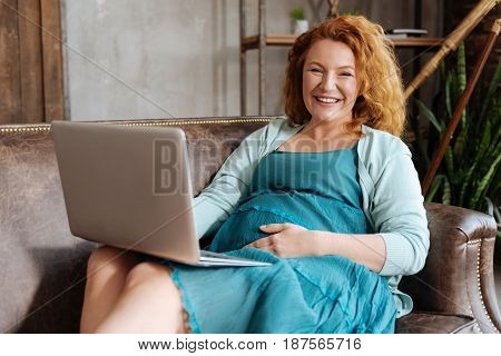 Time to work. Cheerful pregnant woman lying on the sofa, grinning broadly and working on a laptop at home.