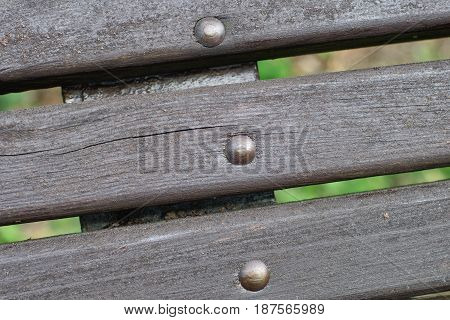 Close up planks from an old wooden bench, situated in the park.