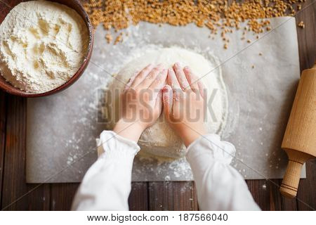 Detail of hands kneading dough on wooden table