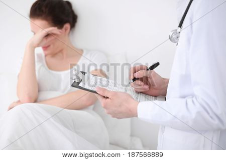 Doctor man is filling up medical history form while consulting patient. Bad news concept