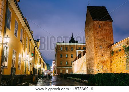 Riga, Latvia - July 3, 2016: Facades Of Old Famous Jacob's Barracks And Part Of Old The City Wall In Torna Street In Lighting At Evening Or Night Illumination In Old Town. Blue Hour