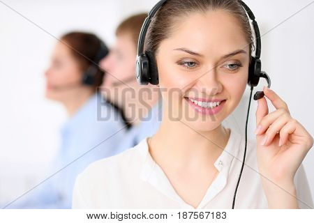 Call center operators. Young beautiful business woman in headset. Male call operator in headset at the background.