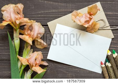 blank white greeting card with tender iris flowers bouquet and envelope with colorful pencils on rustic wooden background. top view. mock up