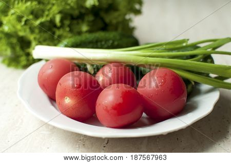 Fresh Organic Tomatoes And Cucumbers With Green Onions On A White Plate