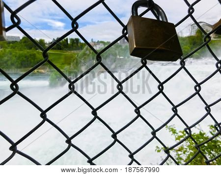 The largest waterfall in Europe by River Rhein in Switzerland. View through the grille and the lock