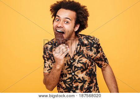 Portrait of a happy young african man eating ice cream isolated over yellow background