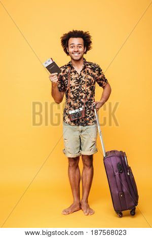 Photo of young happy man standing isolated over yellow background. Looking at camera holding passport and suitcase.