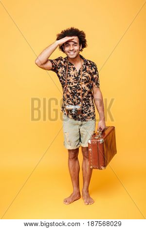 Full length portrait of a cheerful afro american man with suitcase keeping hand on his forehead and looking forward isolated over yellow background