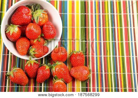 Ripe strawberry on a background of multi-colored sticks
