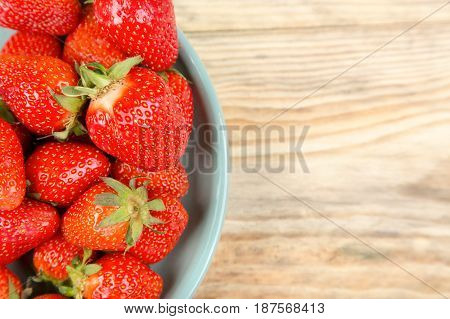 Juicy strawberries in a blue plate on a light wooden background