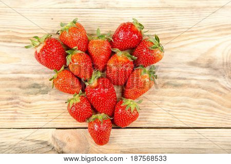 Ripe strawberry in the shape of heart on a background of wood