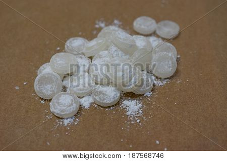 Bunch of white mint candies in powdered sugar on a thin sheet of parchment
