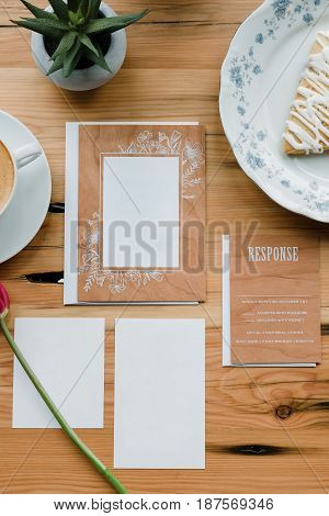 Blank wedding invitation suite made from real wood and photographed in a cafe with coffee on a real wood table top.
