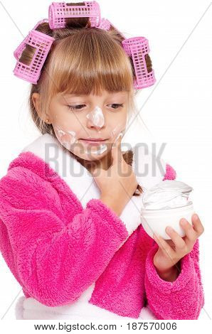 Adorable little girl applying cosmetic cream, isolated on white background