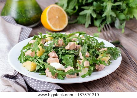 Salad with arugula and egg on a wooden table