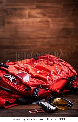 Weather proof backpack, sunglasses and gear for the bicycle on the wooden background. Set of the tourist accessories. Vertical photo. Trip around the world. Preparation and planning for the travelling. Concept of the active lifestyle.