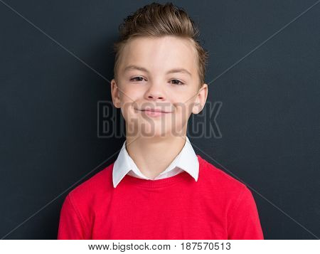 Close-up emotional portrait of caucasian teen boy. Funny teenager looking at camera on black background.