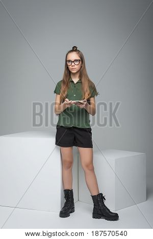 Young beautiful girl with big white cube. woman dressed in green T-shirt, black shorts and large army boots