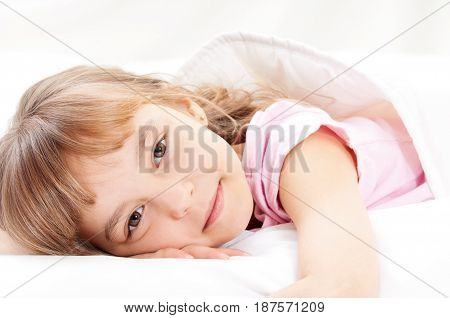 Adorable little girl awaked up in her bed. Close up portrait of happy child, indoor.