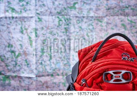 Big tourist orange backpack against map background. Horizontal photo of the bright travelling rucksack. Tourism backgrounds and still-life. Planning and preparation of the trip. Concept of the active lifestyle.