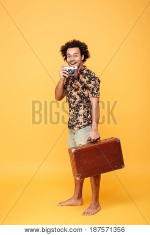 Full length portrait of a smiling cheerful afro american man in summer clothes holding suitcase and retro camera isolated over yellow background