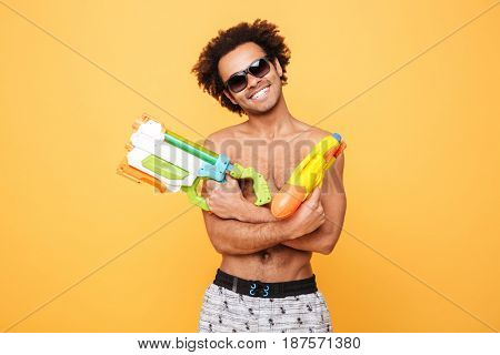 Photo of cheerful young african man dressed in shorts standing isolated over yellow background. Looking at camera holding toy water gun.