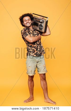 Image of happy african man standing with tape recorder isolated over yellow background. Looking at camera.