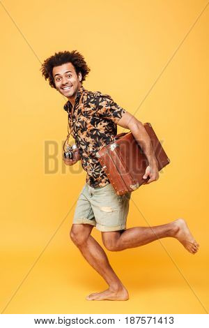 Photo of young happy african man running with suitcase isolated over yellow background. Looking at camera.