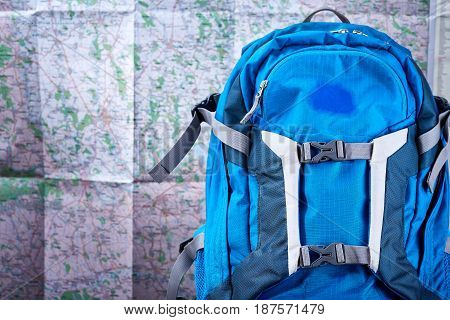 Tourist blue backpack against map background. Horizontal photo of the bright rucksack. Planning and preparation for the travelling. Trip around the world. Travelling backgrounds and still-life. Concept of the active lifestyle.