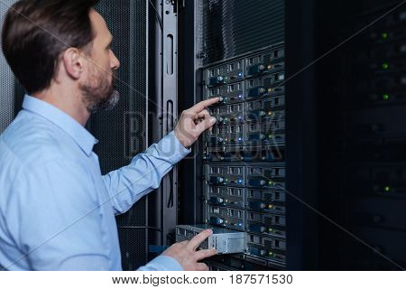 Standard procedure. Nice handsome bearded man standing near the network server and setting it up while doing his job