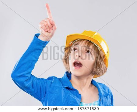 Emotional portrait of caucasian little girl wearing safety yellow hard hat. Shocked or surprised child pointing up and looking away, isolated on white background.