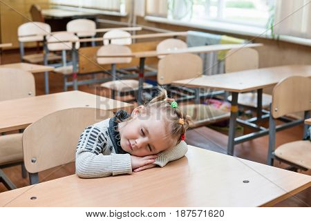 Little charming first-grader is sleeping at school at a desk