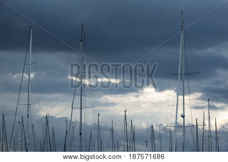 Long shot of sailboat masts against a cloudy stormy Sky
